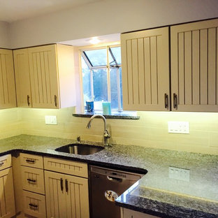 Photo of a mid-sized beach style l-shaped eat-in kitchen in San Diego with an undermount sink, louvered cabinets, beige cabinets, granite benchtops, beige splashback, porcelain splashback, white appliances, laminate floors and a peninsula.