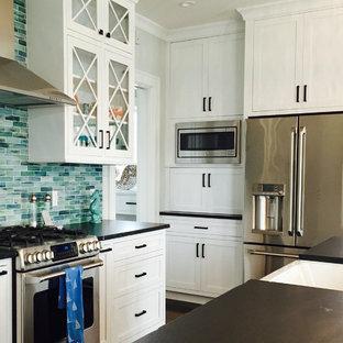 Inspiration för ett mellanstort maritimt kök, med en rustik diskho, skåp i shakerstil, vita skåp, granitbänkskiva, blått stänkskydd, stänkskydd i glaskakel, rostfria vitvaror, mellanmörkt trägolv och en köksö