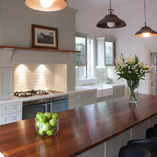 Photo of a large traditional galley separate kitchen in Melbourne with shaker cabinets, wood benchtops, with island, a farmhouse sink, green cabinets, white splashback, terra-cotta splashback, stainless steel appliances and medium hardwood floors.