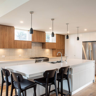 Large contemporary l-shaped open plan kitchen in Melbourne with an undermount sink, flat-panel cabinets, white cabinets, concrete benchtops, beige splashback, ceramic splashback, stainless steel appliances, medium hardwood floors, with island, grey benchtop and brown floor.