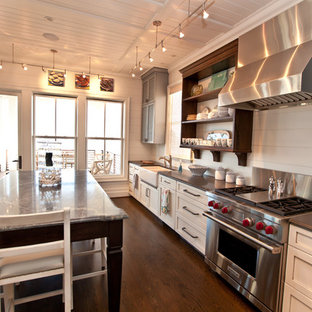 Design ideas for a beach style kitchen in Raleigh with stainless steel appliances, soapstone benchtops, a farmhouse sink, louvered cabinets and grey cabinets.