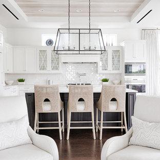Cette image montre une cuisine ouverte marine en L avec un placard à porte vitrée, des portes de placard blanches, une crédence blanche, une crédence en carrelage métro, un électroménager encastrable, un sol en bois foncé, un îlot central et un sol marron.