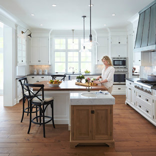 Large coastal open concept kitchen photo in Minneapolis with a farmhouse sink, recessed-panel cabinets, white cabinets, white backsplash, subway tile backsplash and stainless steel appliances