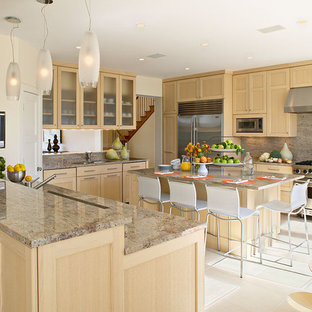 Kitchen - beach style kitchen idea in New York with stainless steel appliances, recessed-panel cabinets, light wood cabinets, granite countertops, brown backsplash and stone slab backsplash