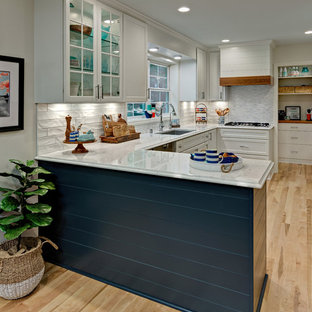 Mid-sized beach style u-shaped light wood floor eat-in kitchen photo in Minneapolis with an undermount sink, flat-panel cabinets, white cabinets, quartz countertops, white backsplash, subway tile backsplash, stainless steel appliances, a peninsula and white countertops