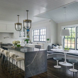 Coastal dark wood floor and brown floor eat-in kitchen photo in Boston with a farmhouse sink, recessed-panel cabinets, white cabinets, white backsplash, stainless steel appliances and an island