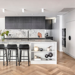 Photo of a beach style l-shaped kitchen in Sydney with black cabinets, marble benchtops, with island, an undermount sink, white splashback, black appliances, light hardwood floors, beige floor and white benchtop.