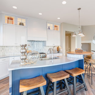 Photo of a large beach style galley open plan kitchen in Chicago with shaker cabinets, white cabinets, matchstick tile splashback, light hardwood floors, with island, a drop-in sink, quartzite benchtops, white splashback and stainless steel appliances.