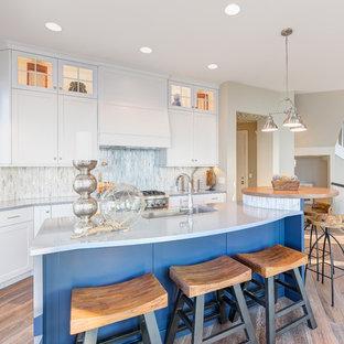 シカゴの大きいビーチスタイルのおしゃれなキッチン (シェーカースタイル扉のキャビネット、白いキャビネット、ボーダータイルのキッチンパネル、淡色無垢フローリング、ドロップインシンク、珪岩カウンター、白いキッチンパネル、シルバーの調理設備の) の写真