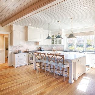 Réalisation d'une cuisine marine en U avec un évier de ferme, un placard avec porte à panneau encastré, des portes de placard blanches, une crédence grise, un électroménager en acier inoxydable, un sol en bois brun et un îlot central.