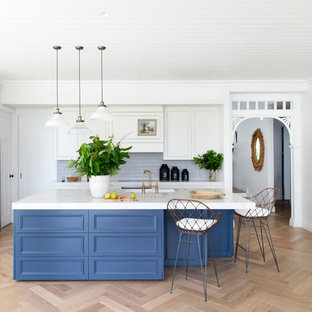 Inspiration for a transitional open plan kitchen in Melbourne with a farmhouse sink, recessed-panel cabinets, white cabinets, blue splashback, light hardwood floors, with island, beige floor and white benchtop.