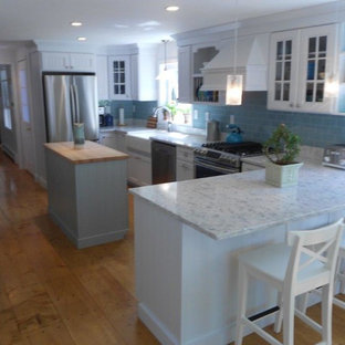 Design ideas for a large beach style u-shaped eat-in kitchen in Portland Maine with a farmhouse sink, louvered cabinets, white cabinets, marble benchtops, blue splashback, subway tile splashback, stainless steel appliances, medium hardwood floors and with island.