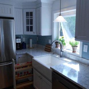 Maritim inredning av ett stort kök, med en rustik diskho, luckor med lamellpanel, vita skåp, marmorbänkskiva, blått stänkskydd, stänkskydd i tunnelbanekakel, rostfria vitvaror, mellanmörkt trägolv och en köksö