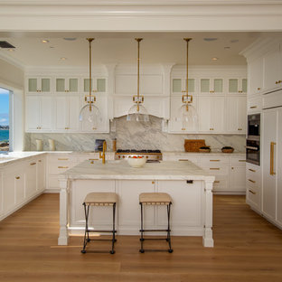 Beach style u-shaped kitchen in Los Angeles with an integrated sink, recessed-panel cabinets, white cabinets, white splashback, window splashback, panelled appliances, medium hardwood floors, with island, brown floor and white benchtop.