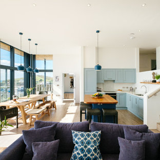Beach style l-shaped open plan kitchen in Cornwall with a submerged sink, shaker cabinets, blue cabinets, white splashback, light hardwood flooring, an island, beige floors and white worktops.