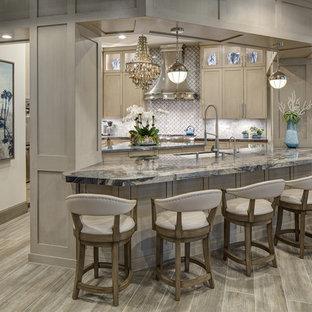 Offene, Mittelgroße Maritime Küche mit Schrankfronten im Shaker-Stil, beigen Schränken, Granit-Arbeitsplatte, Porzellan-Bodenfliesen, Unterbauwaschbecken, Küchenrückwand in Grau, Halbinsel, beigem Boden und bunter Arbeitsplatte in Orange County