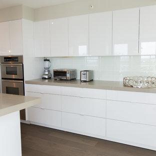 Bild på ett stort funkis kök, med en undermonterad diskho, släta luckor, vita skåp, bänkskiva i kvarts, vitt stänkskydd, rostfria vitvaror, ljust trägolv, stänkskydd i glaskakel och brunt golv
