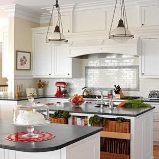 Idéer för avskilda, stora maritima l-kök, med en undermonterad diskho, luckor med profilerade fronter, vita skåp, vitt stänkskydd, stänkskydd i tunnelbanekakel, mellanmörkt trägolv, flera köksöar, bänkskiva i täljsten, rostfria vitvaror och brunt golv