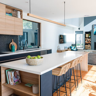 Inspiration for a large beach style galley open plan kitchen in Other with an undermount sink, black cabinets, black splashback, mosaic tile splashback, stainless steel appliances, with island, white benchtop, flat-panel cabinets, medium hardwood floors, brown floor and quartz benchtops.