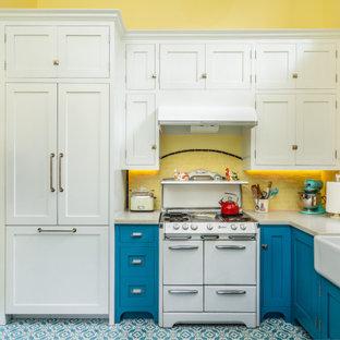 Exemple d'une petite cuisine américaine nature en U avec un évier de ferme, un placard à porte affleurante, des portes de placard bleues, un plan de travail en quartz modifié, une crédence jaune, une crédence en carrelage métro, un électroménager blanc, un sol en carreaux de ciment, un sol bleu et un plan de travail blanc.