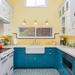 Design ideas for a mid-sized transitional u-shaped eat-in kitchen in Los Angeles with a farmhouse sink, blue cabinets, quartz benchtops, yellow splashback, subway tile splashback, white appliances, cement tiles, blue floor, white benchtop, shaker cabinets and no island.