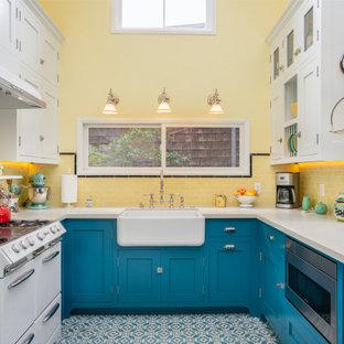 Mittelgroße Klassische Wohnküche ohne Insel in U-Form mit Landhausspüle, blauen Schränken, Quarzwerkstein-Arbeitsplatte, Küchenrückwand in Gelb, Rückwand aus Metrofliesen, weißen Elektrogeräten, Zementfliesen, blauem Boden, weißer Arbeitsplatte und Schrankfronten im Shaker-Stil in Los Angeles