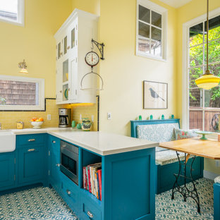 Inspiration for a small country u-shaped eat-in kitchen in Los Angeles with a farmhouse sink, beaded inset cabinets, blue cabinets, quartz benchtops, yellow splashback, subway tile splashback, white appliances, cement tiles, blue floor and white benchtop.