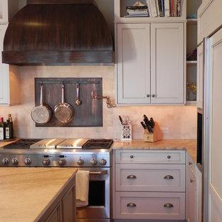 Свежая идея для дизайна: большая п-образная кухня в классическом стиле с техникой под мебельный фасад, мраморной столешницей, фасадами с утопленной филенкой, бежевыми фасадами, обеденным столом, раковиной в стиле кантри, темным паркетным полом, островом, бежевым фартуком, фартуком из травертина и коричневым полом - отличное фото интерьера