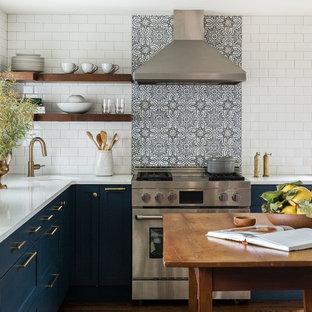 Inredning av ett lantligt l-kök, med en undermonterad diskho, skåp i shakerstil, blå skåp, blått stänkskydd, rostfria vitvaror, mörkt trägolv och en köksö