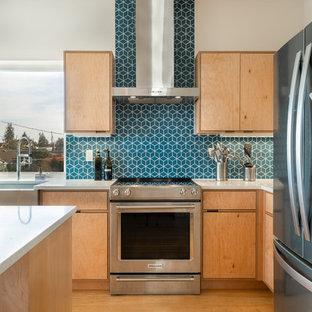 Пример оригинального дизайна: угловая кухня-гостиная среднего размера в стиле модернизм с раковиной в стиле кантри, плоскими фасадами, светлыми деревянными фасадами, столешницей из кварцевого композита, синим фартуком, фартуком из цементной плитки, техникой из нержавеющей стали, полом из бамбука, островом, коричневым полом и белой столешницей