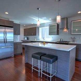 シアトルの小さいコンテンポラリースタイルのおしゃれなキッチン (アンダーカウンターシンク、フラットパネル扉のキャビネット、茶色いキャビネット、人工大理石カウンター、緑のキッチンパネル、ガラスタイルのキッチンパネル、シルバーの調理設備、濃色無垢フローリング、茶色い床) の写真