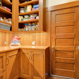 This is an example of a mid-sized l-shaped kitchen pantry in Seattle with a farmhouse sink, recessed-panel cabinets, medium wood cabinets, wood benchtops, orange splashback, timber splashback, medium hardwood floors, no island, orange floor and orange benchtop.