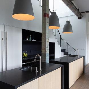 ニューヨークの中サイズのインダストリアルスタイルのおしゃれなキッチン (黒いキッチンカウンター、無垢フローリング、一体型シンク、オープンシェルフ、黒いキャビネット、人工大理石カウンター、シルバーの調理設備の、茶色い床) の写真