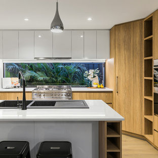 Inspiration for a contemporary u-shaped kitchen in Perth with a double-bowl sink, flat-panel cabinets, light wood cabinets, window splashback, light hardwood floors, beige floor and white benchtop.