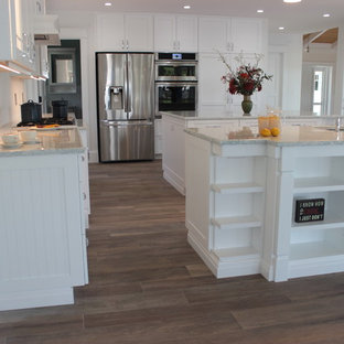 Large beach style single-wall open plan kitchen in Miami with white cabinets, quartz benchtops, white splashback, stainless steel appliances, ceramic floors, multiple islands, a double-bowl sink and shaker cabinets.