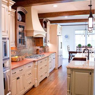 Offene, Einzeilige, Große Klassische Küche mit Landhausspüle, Kassettenfronten, weißen Schränken, Granit-Arbeitsplatte, bunter Rückwand, Rückwand aus Keramikfliesen, Küchengeräten aus Edelstahl, braunem Holzboden und Kücheninsel in Sonstige