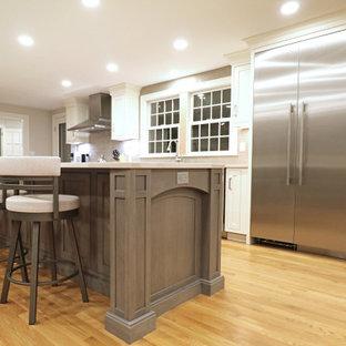Klassisk inredning av ett mellanstort vit linjärt vitt kök och matrum, med en rustik diskho, luckor med profilerade fronter, vita skåp, bänkskiva i kvarts, grått stänkskydd, stänkskydd i keramik, rostfria vitvaror, ljust trägolv, en köksö och gult golv
