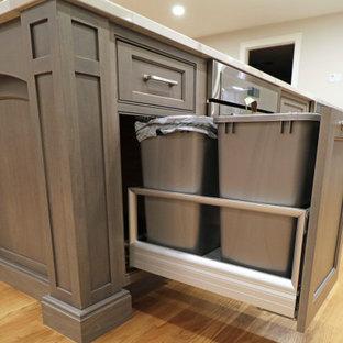 ボストンの中くらいのトランジショナルスタイルのおしゃれなキッチン (エプロンフロントシンク、インセット扉のキャビネット、白いキャビネット、クオーツストーンカウンター、グレーのキッチンパネル、セラミックタイルのキッチンパネル、シルバーの調理設備、淡色無垢フローリング、黄色い床、白いキッチンカウンター) の写真