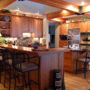 This is an example of a country kitchen in Chicago with stainless steel appliances, shaker cabinets, medium wood cabinets, multi-coloured splashback and slate splashback.