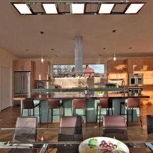 Cette image montre une grande cuisine américaine linéaire design avec un évier encastré, un placard à porte plane, des portes de placard turquoises, un plan de travail en bois, une crédence beige, un électroménager en acier inoxydable, un sol en bois brun, un îlot central, un sol beige et un plan de travail beige.