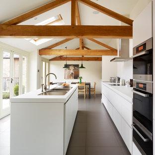ハンプシャーの中くらいのカントリー風おしゃれなアイランドキッチン (ダブルシンク、フラットパネル扉のキャビネット、白いキャビネット、珪岩カウンター、シルバーの調理設備、グレーの床、白いキッチンカウンター、白いキッチンパネル) の写真