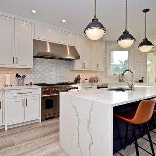 Large coastal eat-in kitchen ideas - Eat-in kitchen - large coastal u-shaped porcelain floor and beige floor eat-in kitchen idea in Tampa with a single-bowl sink, beaded inset cabinets, white cabinets, quartz countertops, white backsplash, ceramic backsplash, stainless steel appliances, an island and white countertops