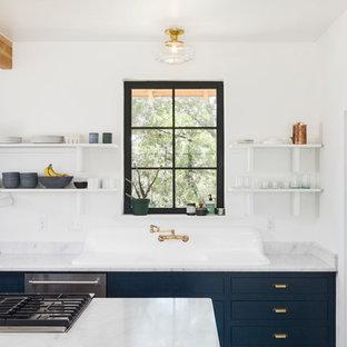 Modelo de cocina campestre con armarios con paneles lisos, una isla, fregadero encastrado, puertas de armario azules y salpicadero de vidrio