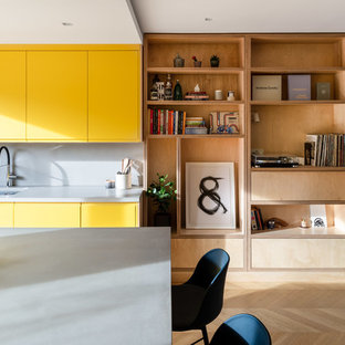 Design ideas for a contemporary kitchen/diner in London with a submerged sink, flat-panel cabinets, yellow cabinets, grey splashback, light hardwood flooring, an island, beige floors and grey worktops.