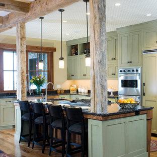 Imagen de cocina rústica con electrodomésticos con paneles, armarios con paneles empotrados y puertas de armario verdes