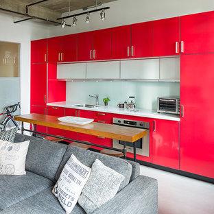 Offene, Zweizeilige, Kleine Industrial Küche mit Doppelwaschbecken, flächenbündigen Schrankfronten, roten Schränken, Glasrückwand, Küchengeräten aus Edelstahl, Betonboden, Kücheninsel, Quarzit-Arbeitsplatte und Küchenrückwand in Weiß in Vancouver