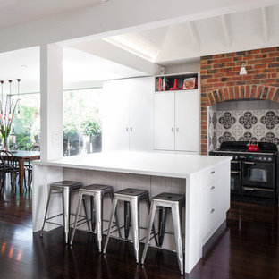 Design ideas for a large contemporary l-shaped eat-in kitchen in Melbourne with dark hardwood floors, with island and black appliances.