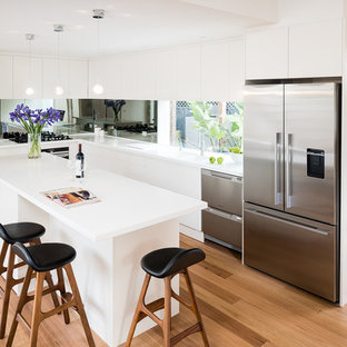 Inspiration for a mid-sized contemporary l-shaped eat-in kitchen in Melbourne with an integrated sink, flat-panel cabinets, white cabinets, solid surface benchtops, mirror splashback, stainless steel appliances, medium hardwood floors, with island, metallic splashback and white benchtop.