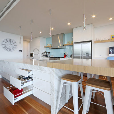 Kitchen - contemporary galley kitchen idea in Melbourne with an undermount sink, flat-panel cabinets, white cabinets, wood countertops, blue backsplash, glass sheet backsplash and stainless steel appliances