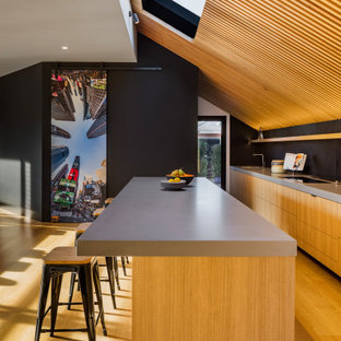 Large contemporary galley open plan kitchen in Melbourne with solid surface benchtops, with island, brown floor, grey benchtop, flat-panel cabinets, medium wood cabinets and medium hardwood floors.
